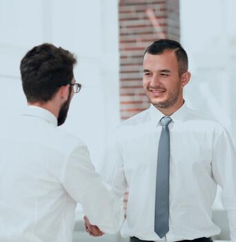 Zwei Geschäftsleute geben sich die Hände.