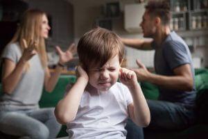 Ein Kind, dass sich gestresst die Ohren zuhält und die Augen zukneift, während sich im Hintergrund ein Paar streitet.