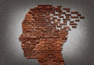 Eine Ziegelsteinmauer in Form eines menschlichen Kopfes, die sich auflöst.